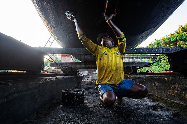 A Worker Brushes Bitumen on to the Bottom of a Fishing Boat
