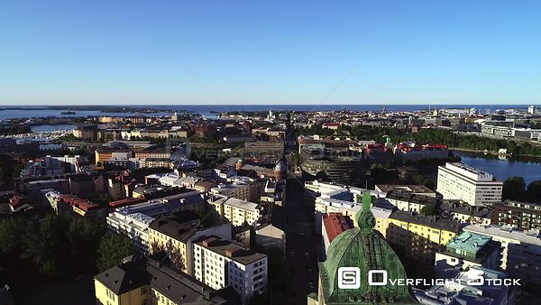 Helsinki city, UHD aerial view over the cityscape, revealing the kallio church, on a sunny summer morning dawn, in Helsingfor...