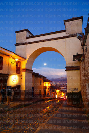 Full moon rising, seen through archway at top of Cuesta Santa Ana street at twilight, Cusco, Peru