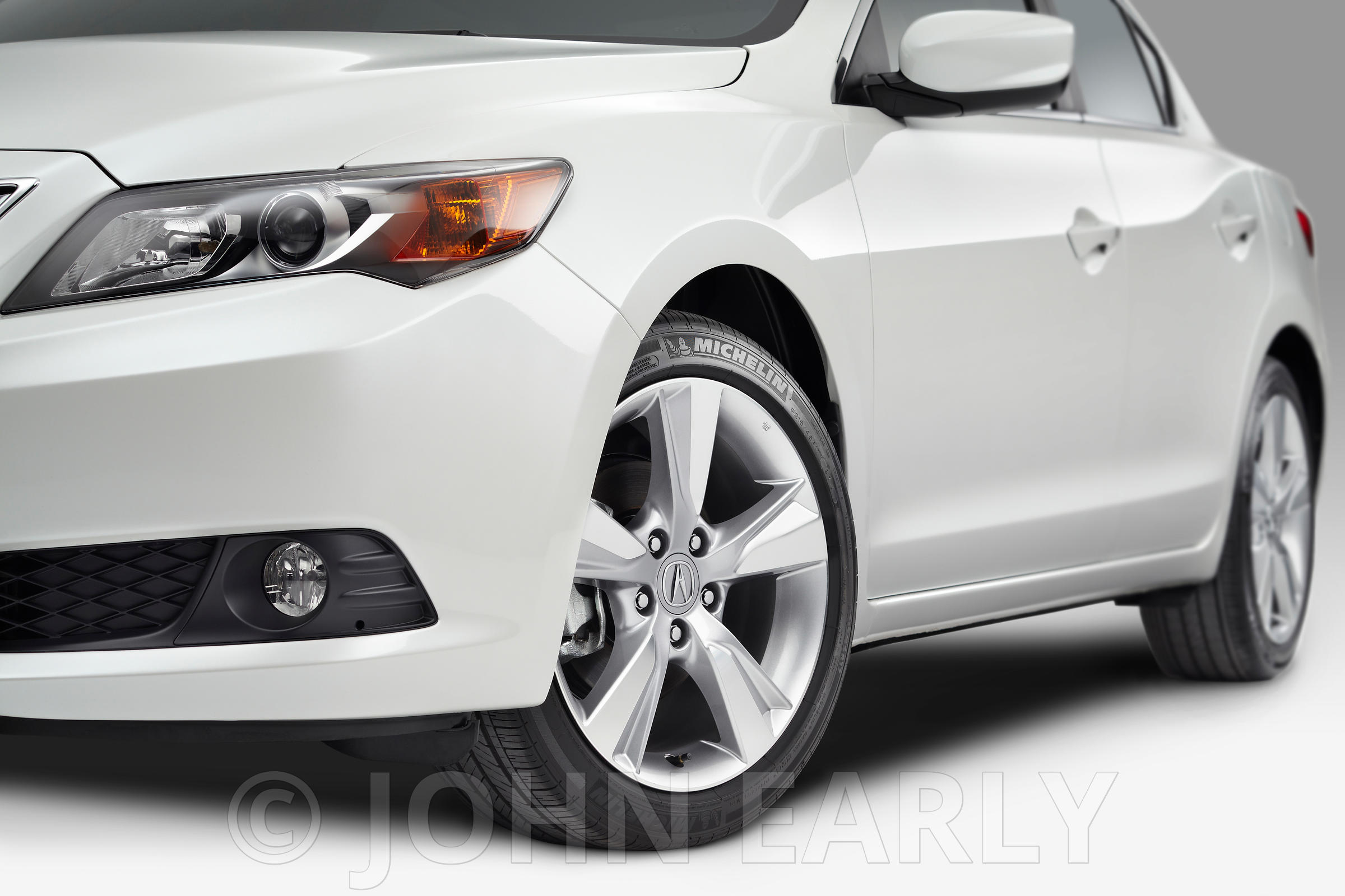 Detail 3/4 Front Shot of White Sedan With Focus on Tires and Wheels