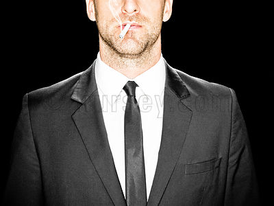 image of a male in a black suit against a black background with a cigarette in his mouth looking straight at camera, cropped ...