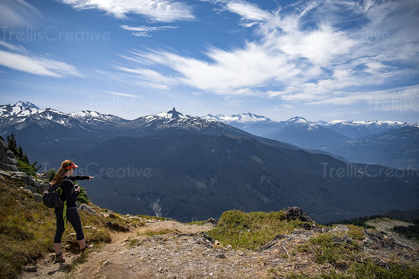 Woman hiker pointing the way on remote mountain trail, Blackcomb Mountain, Whistler, Canada.