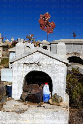 Offering of bottle of Ceibo alcohol on tomb in Milluni cemetery, Bolivia