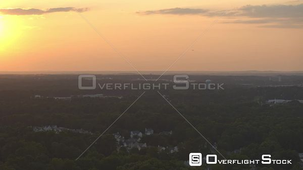 Atlanta Panning toward airport at sunset with surrounding cityscape in foreground and plane in air