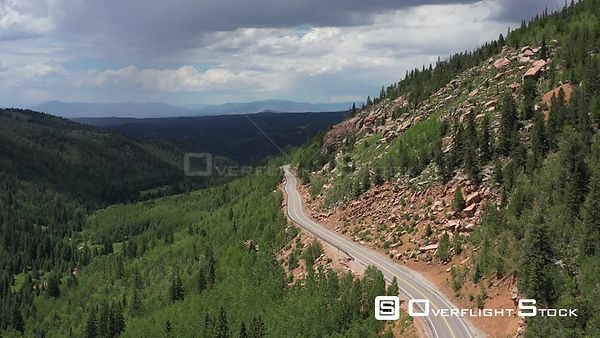 Rocky Mountain slope, curvey highway,  clouds and rain shafts, Teller County, Colorado, USA