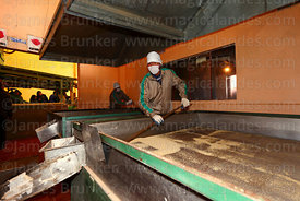 man working at a machine for separating quinoa seeds in a processing plant, Salinas de Garci Mendoza, Bolivia