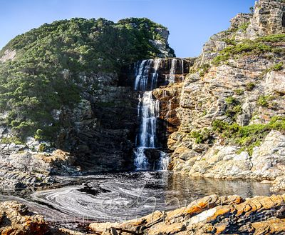 Waterfall cascading into a natural dark rock pool with beautiful white foam swirls, surrounded by indigenous coastal fynbos.