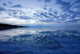 Salt formations and clouds reflected in surface of Salar de Uyuni in rainy season at twilight, Bolivia