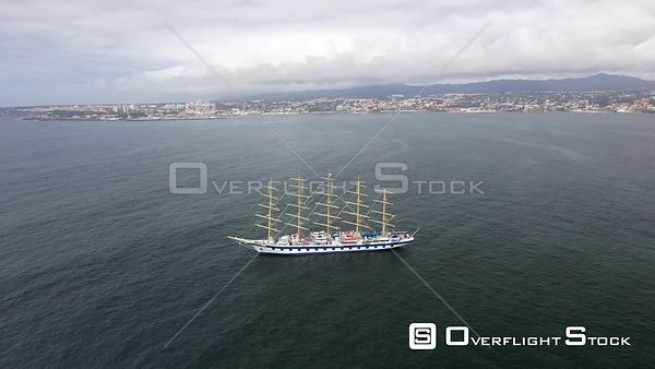 Aerial reverse tracking over Royal Clipper at Cascais coast, on a  partly sunny day, in Lisbon, Portugal - anchored due to th...