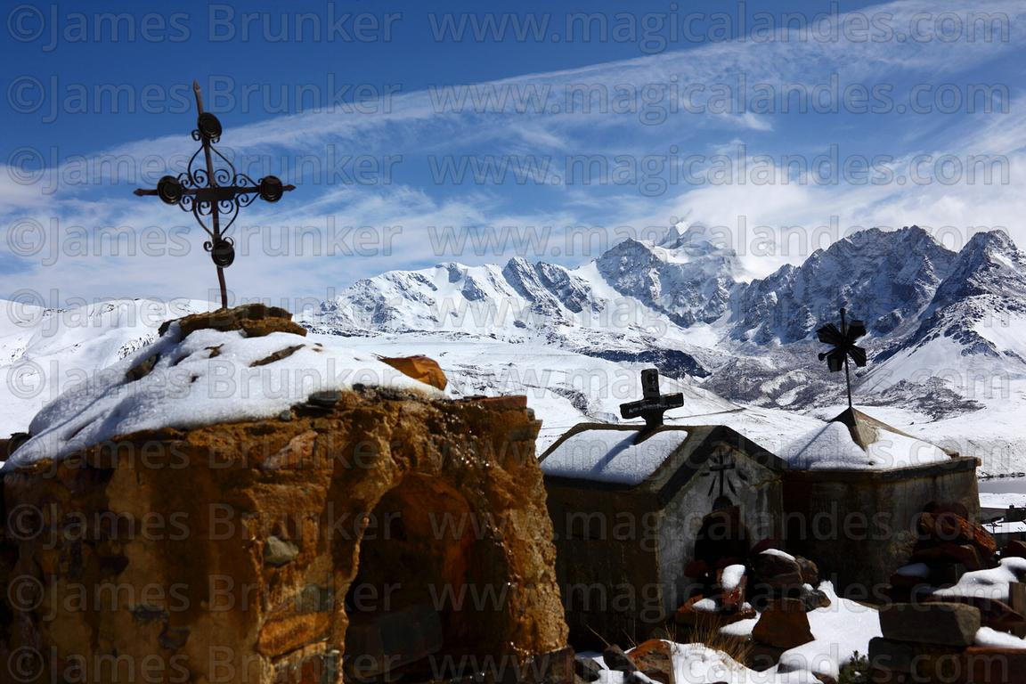 Tombs in Milluni cemetery after winter snowfall, Mt Huayna Potosi in background, Cordillera Real, Bolivia