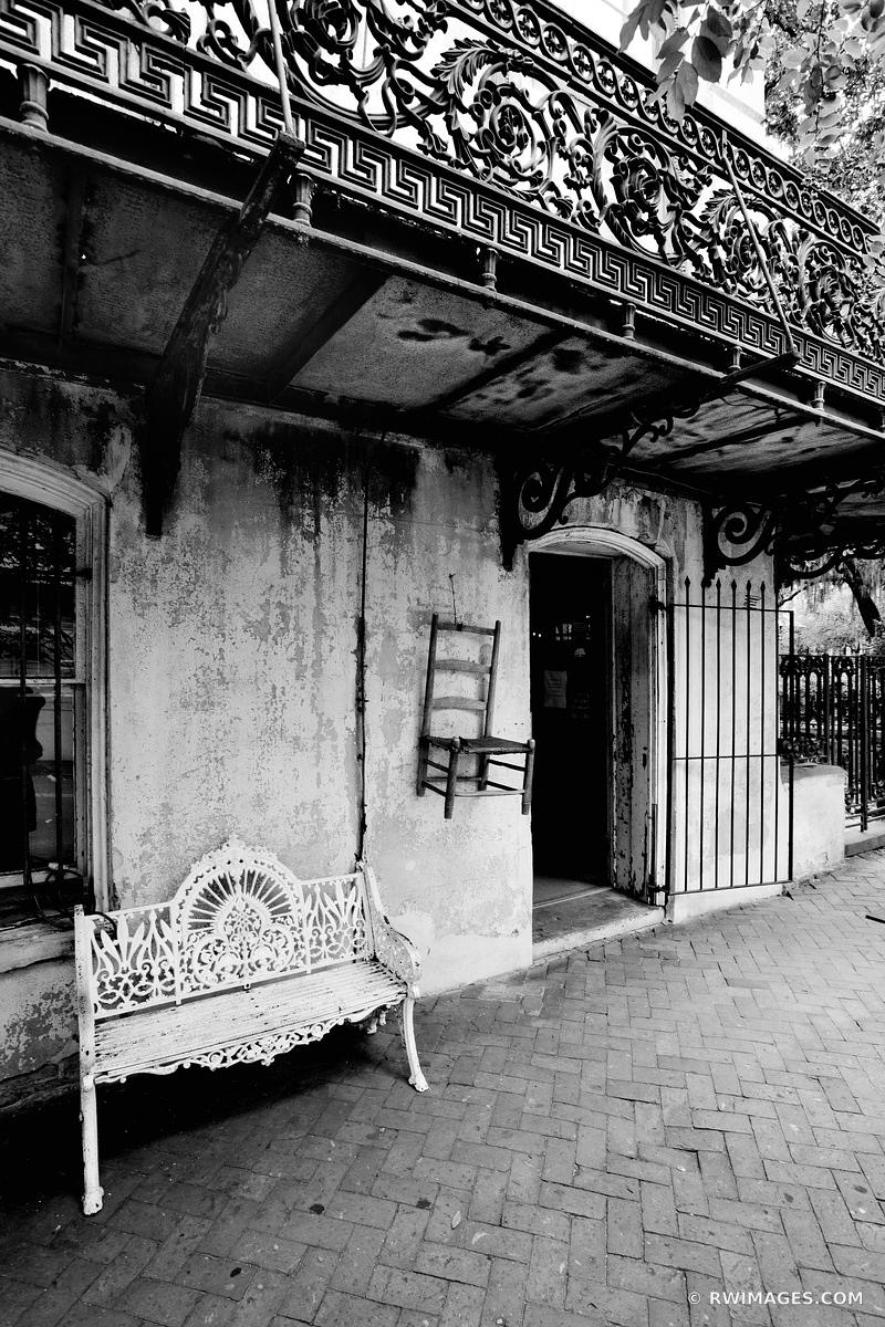 OLD IRON BENCH UNDER BALCONY HISTORIC SAVANNAH GEORGIA BLACK AND WHITE VERTICAL