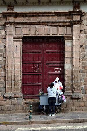Woman selling hot drinks from stall in front of colonial doorway, Cusco, Peru