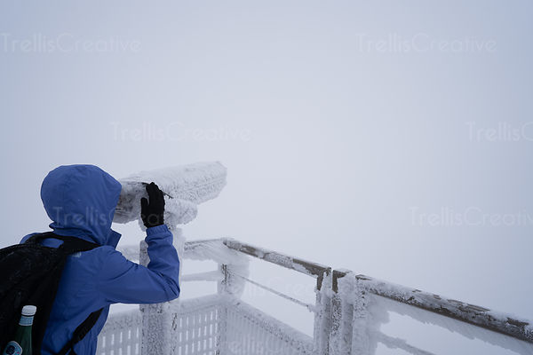 Tourist looks through ice covered binoculars into a foggy abyss.