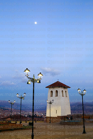 Full moon rising above Santa Ana church belfry and Plaza Santa Ana at twilight, Cusco, Peru