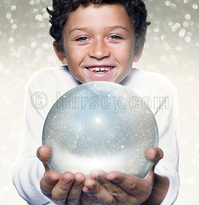 mixed race young boy holding a crystal ball smiling at camera