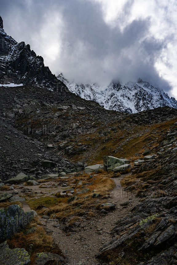 A rocky trail in the French Alps leads to snow-capped jagged mountain peaks