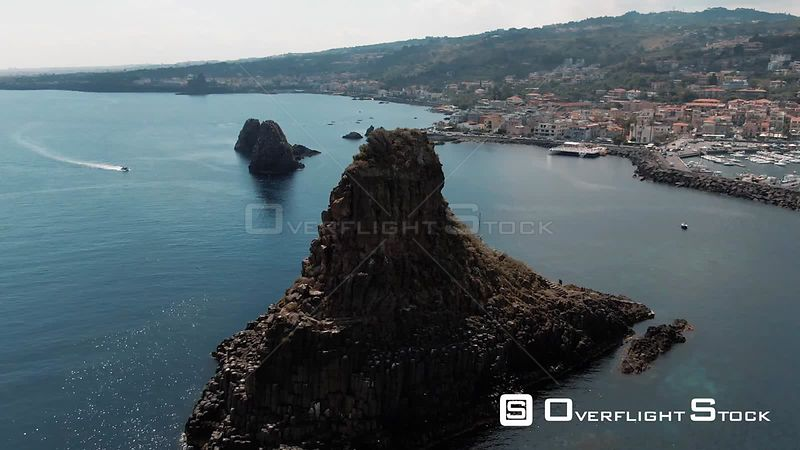 Aerial orbiting view of the faraglioni and the fishing village of Acitrezza on the East coast of Sicily. Italy