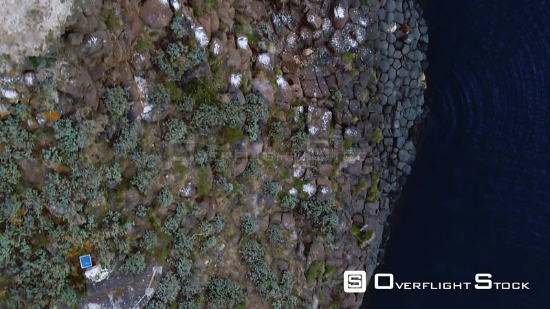 Aerial top down close up view of faraglione grande, a basalt volcanic formation on the sea by the East coast of Sicily. Italy