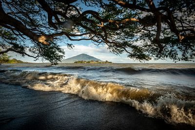 Small waves roll onto the shore of Ometepe Island with view of Volcano Maderas in background.