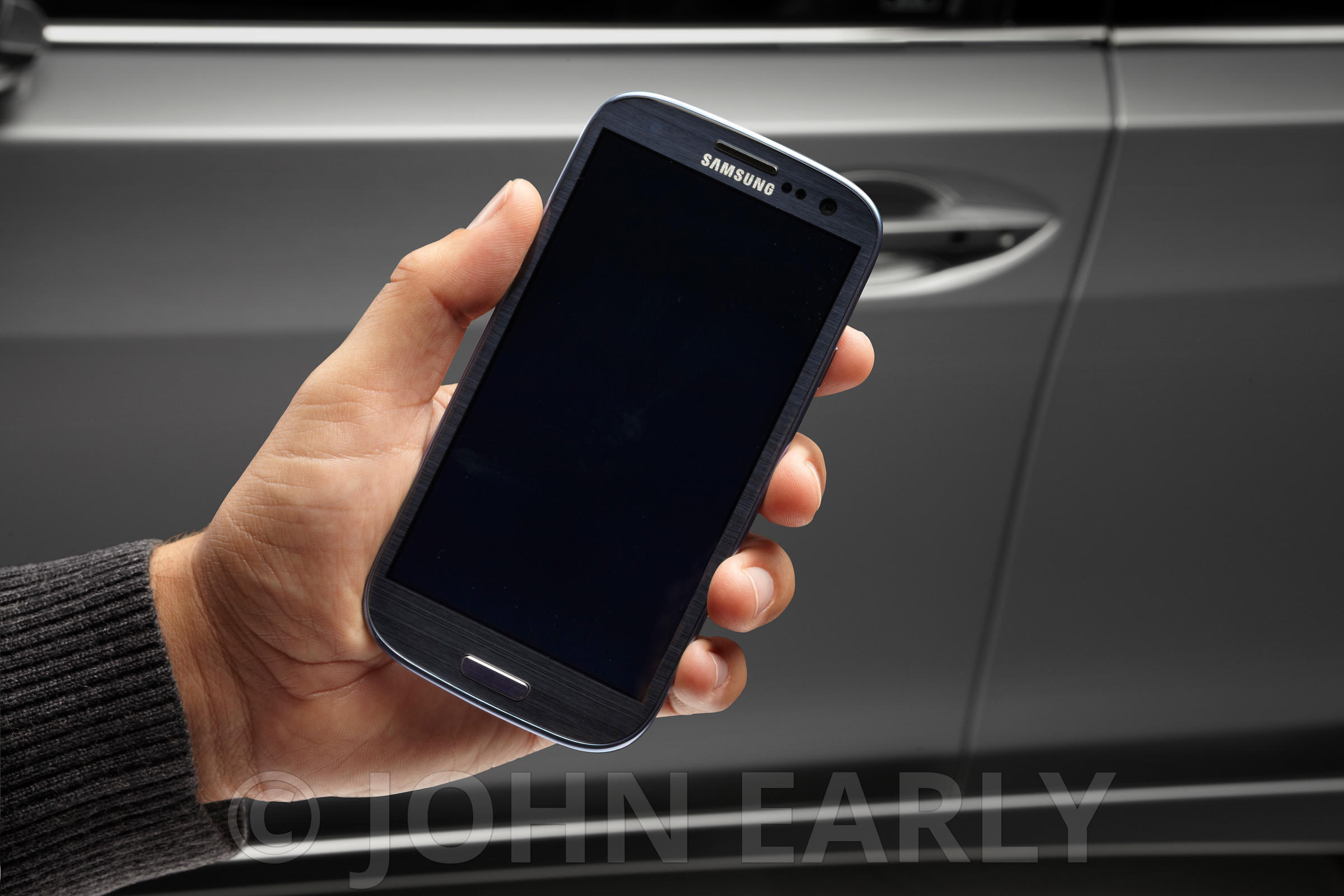 Male Hand Holding Samsung Phone With Car Background