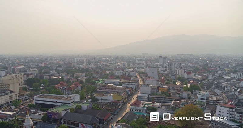 Chang Mai Thailand Aerial Flying through city toward mountains following path of road