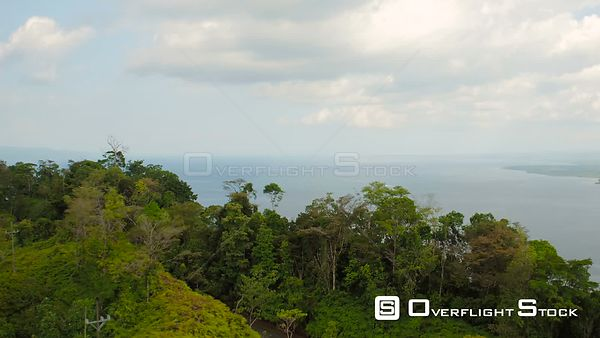 Flying low over dense jungle forests towards large ocean bay. Costa Rica