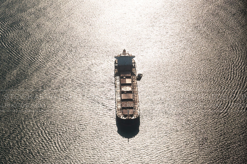 Cargo ship with the suns reflection