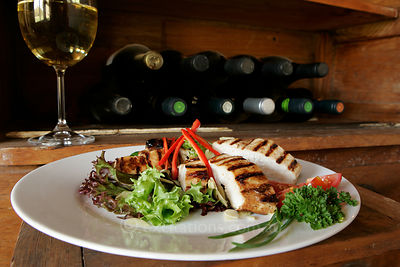 Grilled chicken salad in rustic setting.