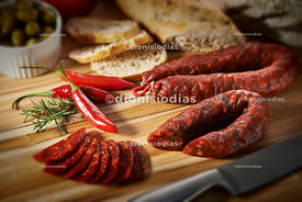Spanish spicy salame, sliced and on wood background.