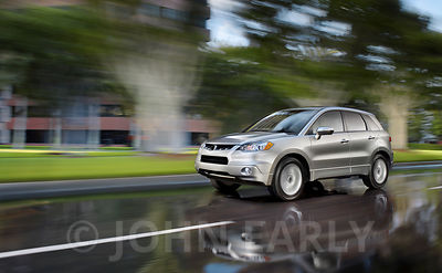 Silver SUV Driving Action 3/4 Front With Green Business Park Background