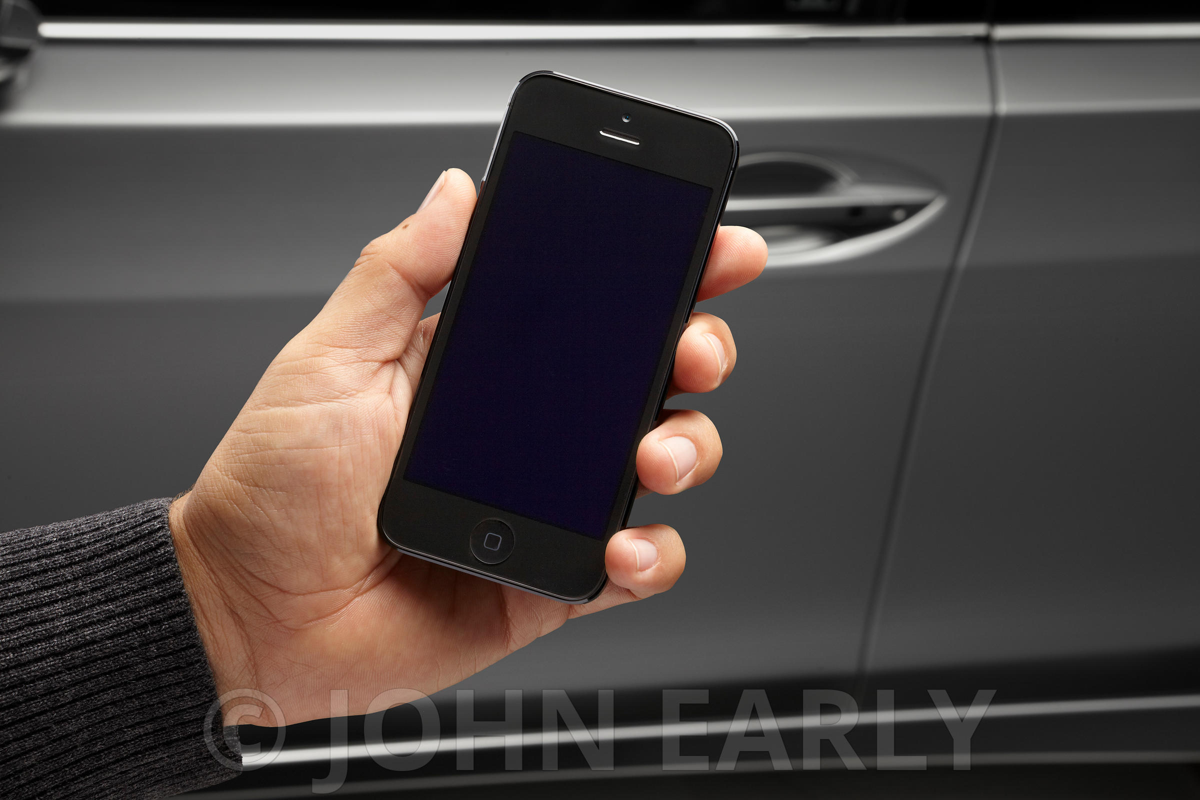 Male Hand Holding IPhone 6 With Car Background