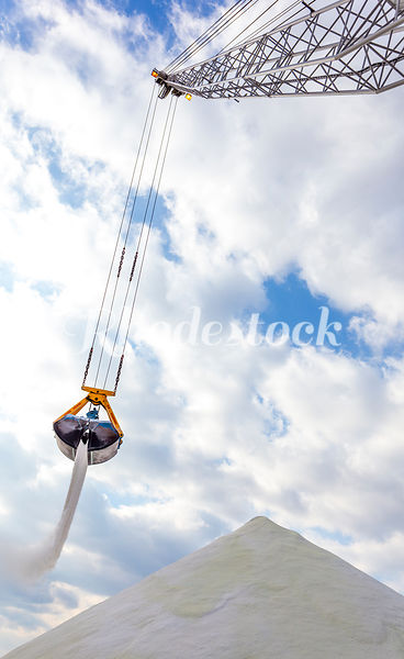 A crane unloading bulk salt from a ship drops a swinging bucket full of a salt onto a large pile with the blue sky in the bac...