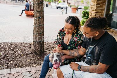 Silly Dog and Family Sit Outside in City Downtown