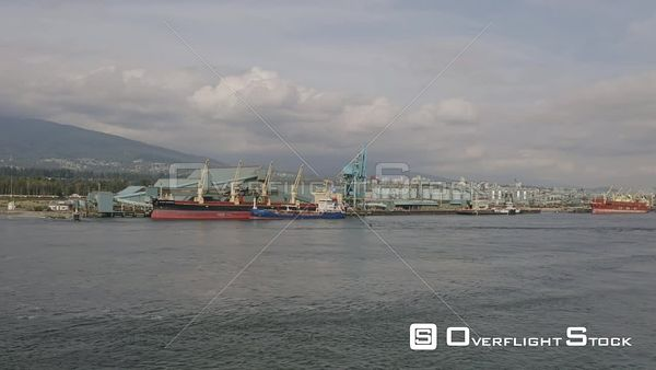 Vancouver BC Canada Low vantage panning view of industrial shipping terminal with downtown cityscape afar