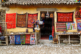 Weavings for sale hanging outside rustic shop, Ollantaytambo, Sacred Valley, Peru