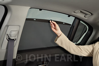 Detail of Woman's Hand Closing Rear Sunshade in Luxury Sedan