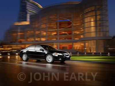 Black Sedan in Driving Action At Night With HIgh Rise Building in Background