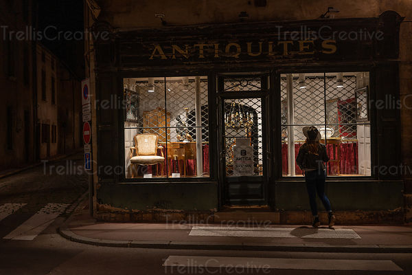 A yound stylish woman looks in the window of a French antique shop in Beaune, France