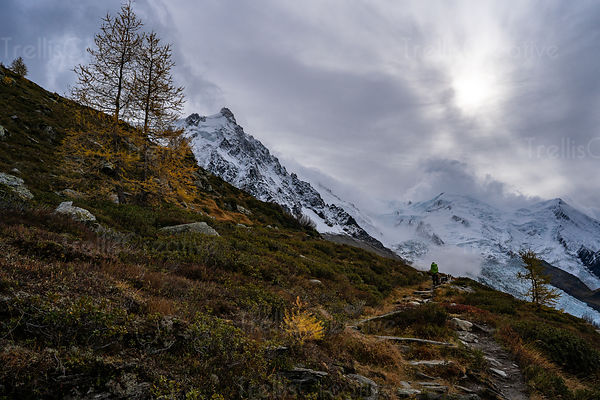 A backpacker and her dog hike along a rocky trail leading to the Mont Blanc mountain glacier in the Alps