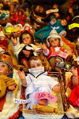 Baby Jesus figure dressed as a doctor and wearign a surgical mask on sale in a Christmas market with more traditionally dress...