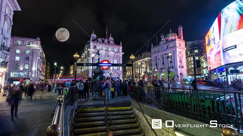 Timelapse view of Piccadilly Circus in London at night with full moon raising