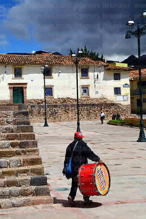 Man carrying drum across Plaza Santa Ana, Cusco, Peru