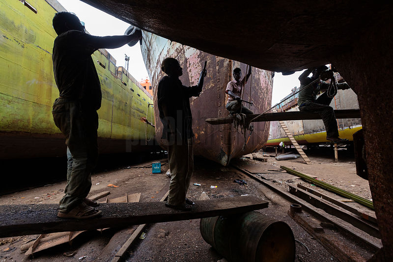 Shipyard Workers Removing Rust from the Hull of a Ship