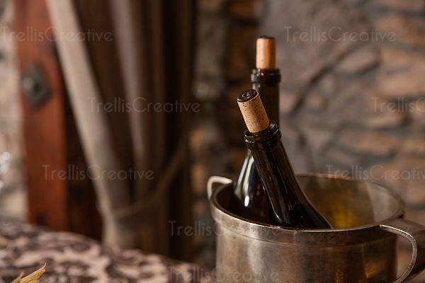 Close up of two wine bottles in a metal wine bucket.