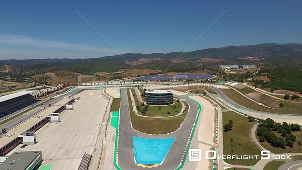 Aerial reverse drone shot from the middle of Algarve International Circuit on a sunny day, in Portimão, Portugal