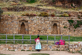 Aymara woman waiting for boat in front of restored double-jamb niches in Inca wall next to main port below Yumani , Sun Islan...