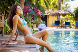 Ethnic woman relaxing by the pool