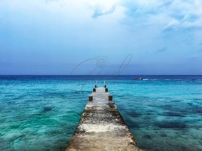 Pier on Caribbean Sea With Boat