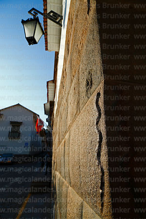 Street light and snake carved in Inca stonework of the Nazarenas Palace, Cusco, Peru