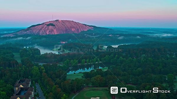 Approach of Stone Mountain from the north at sunrise over Stone Mountain Golf Course and lake. Georgia